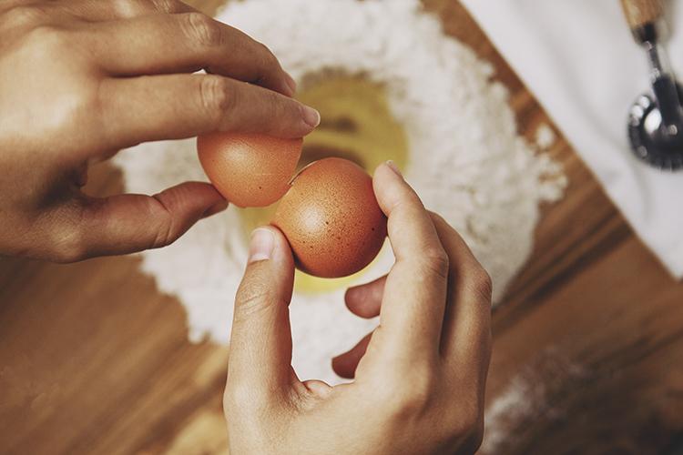 hands cracking eggs into flour