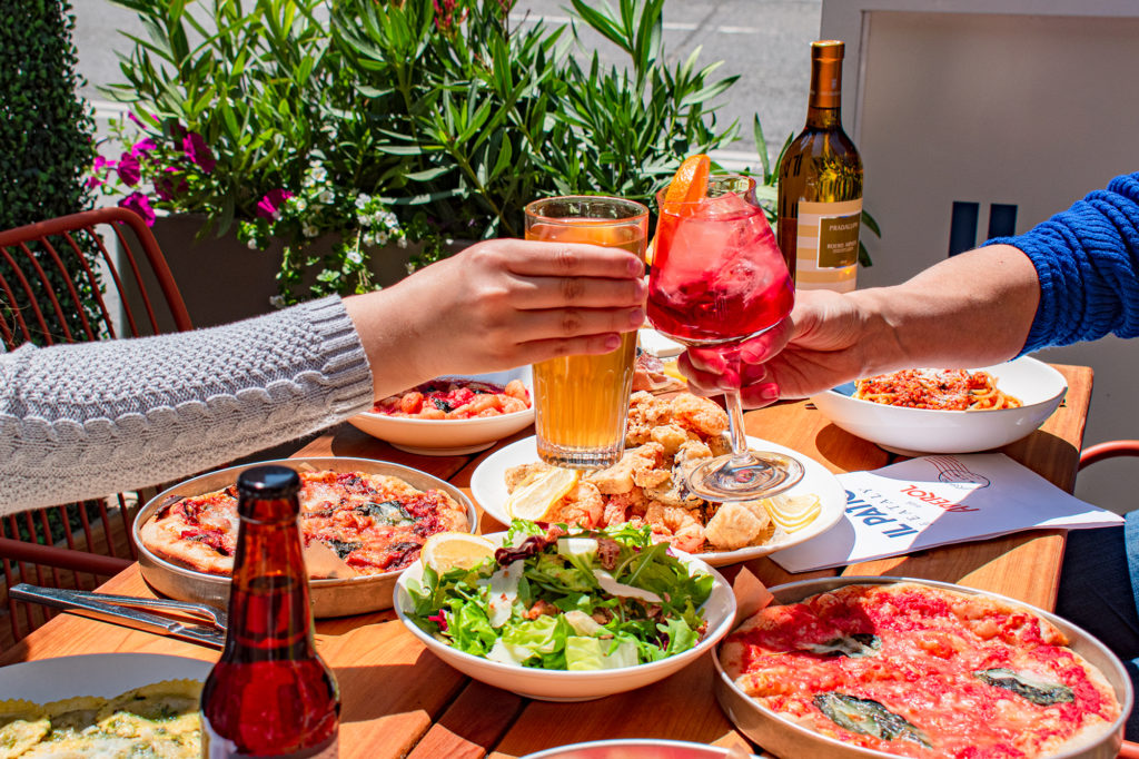 Beer and Aperol Spritz cheers outdoors at Il Patio di Eataly with Aperol