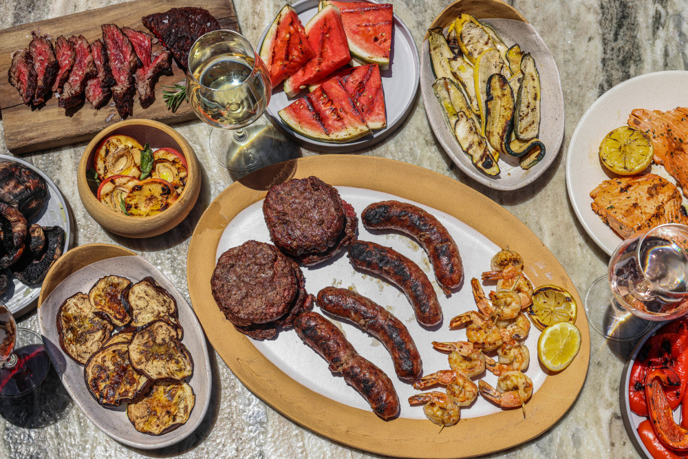 grilled meat, seafood, and produce on a table