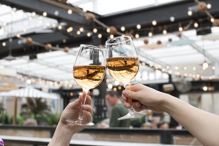 2 people clinking glasses of rosé