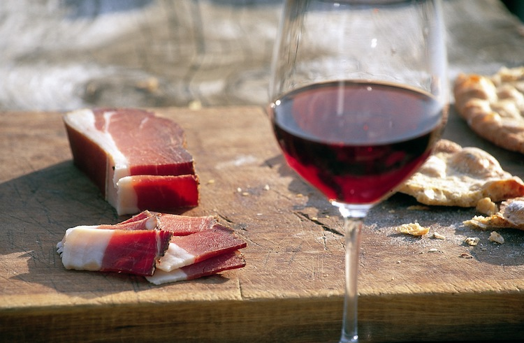 Speck on a board with a glass of red wine