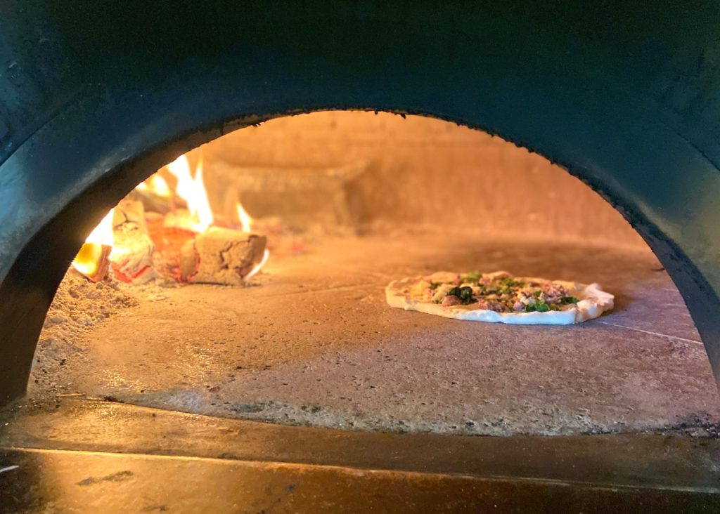 Neapolitan pizza cooking in a wood-fire oven